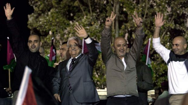 Welcome ceremony: Palestinian President Mahmoud Abbas, second left, and freed prisoners greet the crowd at the ...