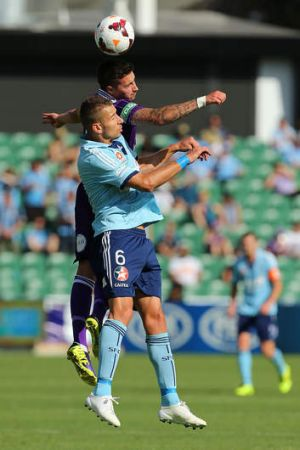Jamie Maclaren of the Glory and Nikola Petkovic of Sydney FC contest the ball.