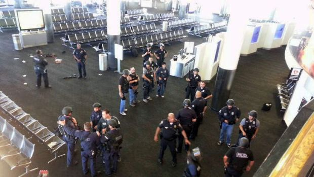 Lockdown: Police stand near the location of an unidentified weapon in terminal three of LAX airport.