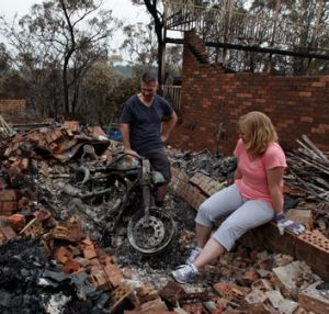 Paul and Karen Bousfield inspect the charred remains of Paul's motorcycle in Buena Vista Rd, Winmalee.