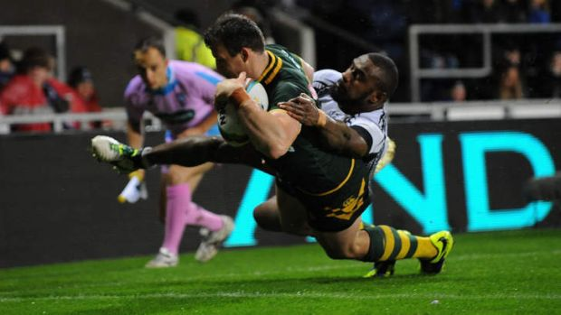 Twin power: Kangaroos centre Josh Morris crosses for a second-half try against Fiji.