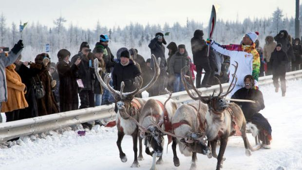 The Sochi 2014 Winter Olympic torch is carried by a torchbearer riding atop a deer sleigh in the West Siberian town of ...