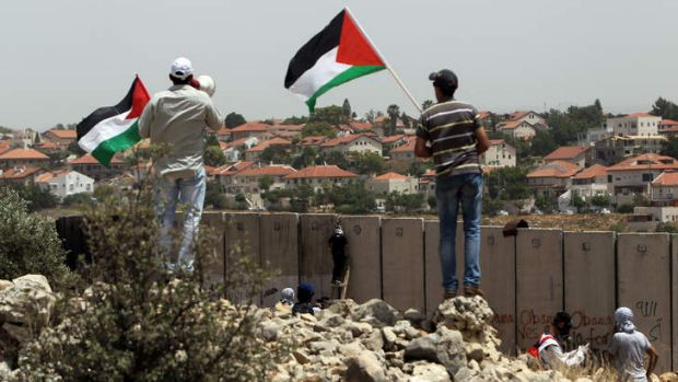 Dividing line: Palestinian protesters wave their national flag as their comrades climb Israel's controversial separation ...