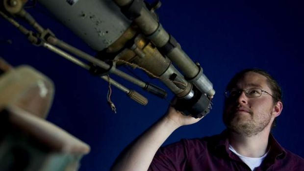 Astronomer Dr Brad Tucker stands with one of the oldest telescopes in Australia, built in 1886 at Mount Stromlo.