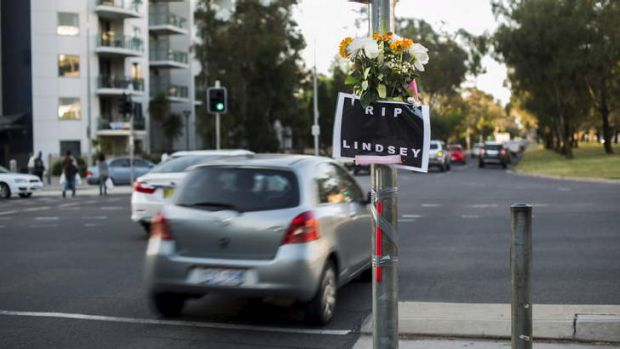 A sign and flowers at the intersection of Barry Dr and Northbourne Ave for well-known Canberra window-washer, Lindsay.