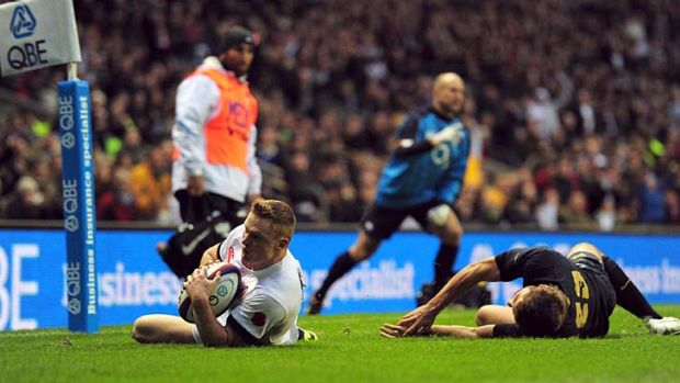 Chris Ashton of England beats the tackle of Santiago Cordero of Argentina to score a try.