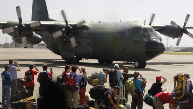 Local and foreign medical teams prepare to board a Philippines air force C-130 transport plane in Manila.