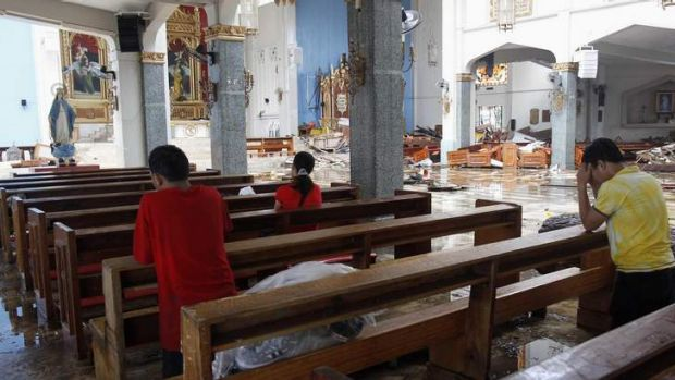 Residents pray inside a damaged Catholic Church after super Typhoon Haiyan battered Tacloban city.