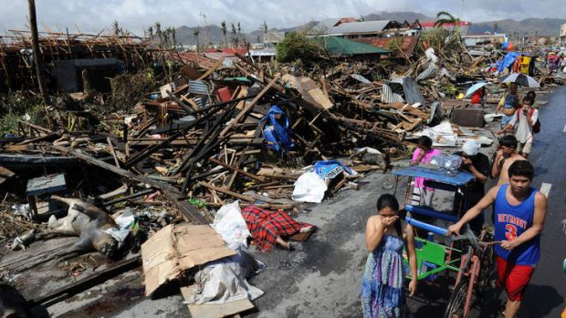Residents walk past bodies and destroyed houses in Tacloban, the Philippines.