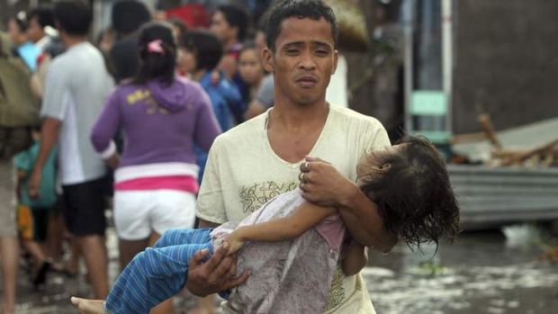 A father carries the lifeless body of his daughter on the way to the morgue after super typhoon Haiyan hit Tacloban City ...