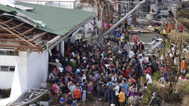 Residents queue up to receive treatment and relief supplies at Tacloban airport following Friday's Typhoon Haiyan that ...