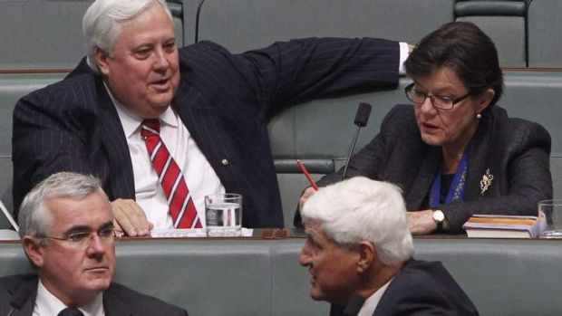 Palmer United Party MP Clive Palmer takes his seat in Parliament next to Indi indpendent Cathy McGowan with Andrew ...