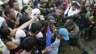 Typhoon survivors jostle to get on board a C-130 military transport plane.