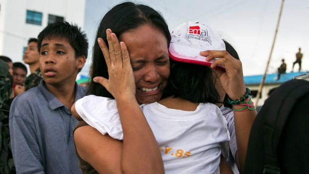 A woman carrying a child cries as other survivors of Typhoon Haiyan wait to board a C130 aircraft during the evacuation ...