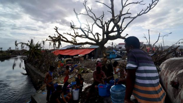 Survivors collect water from a broken water pipe in an area devastated by Typhoon Haiyan.
