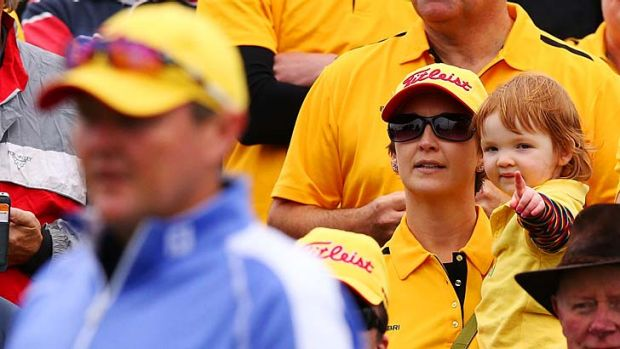 Jarrod Lyle's daughter Lusi Lyle and wife Briony Lyle watch his shot on the first tee .