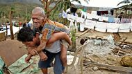 Grandson Joel Asoque carries his 87 yrs of age blind grandfather Francisco  Mainit of Lat-Osan village Palompon Leyte ...