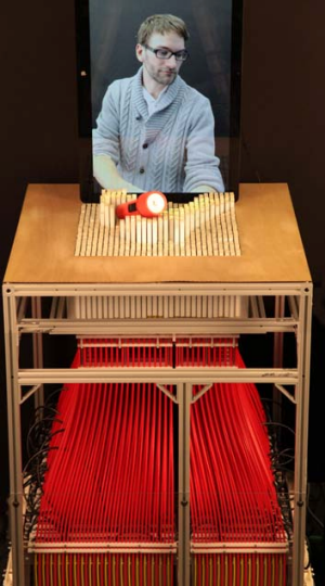A person remotely manipulates an object using the inFORM.