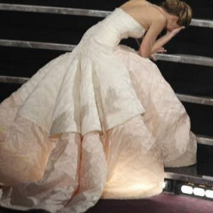 Jennifer Lawrence falls on her way to the stage to receive the award for best actress for her role in the <i>Silver ...