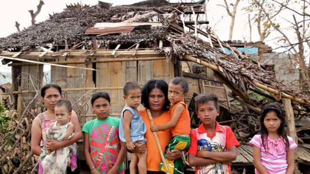 Left with nothing: Marina Pintoy, middle, with her children outside their destroyed house.