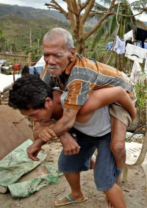 Miracle: Joel Asoque carries his blind grandfather.