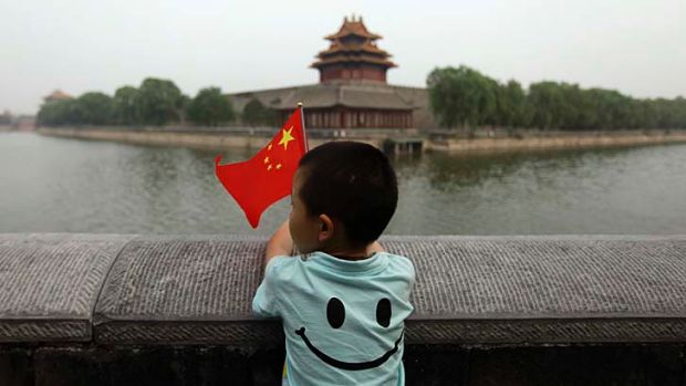 A young boy holds his country's flag: China is set to relax its one-child policy.