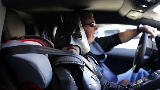 """Miles Scott, 5, dressed as Batkid, waits in a Lamborghini """"Batmobile"""" as he and Batman get ready to stop a bank robbery ..."""