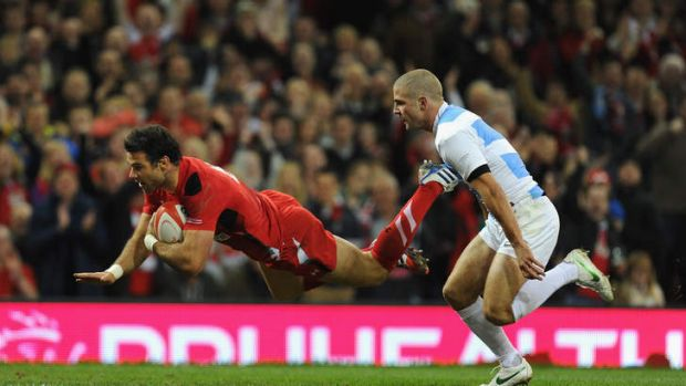 Mike Phillips outpaces Santiago Cordero of Argentina to score Wales' first try.