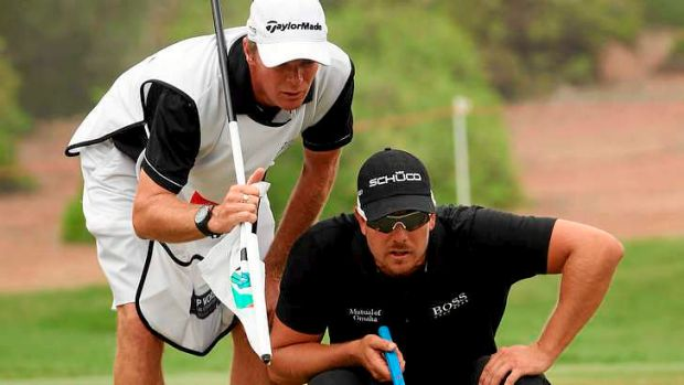 Henrik Stenson lines up a putt on the 11th hole with help from Gareth Lord. The caddy bought a Ferrari on the back of ...