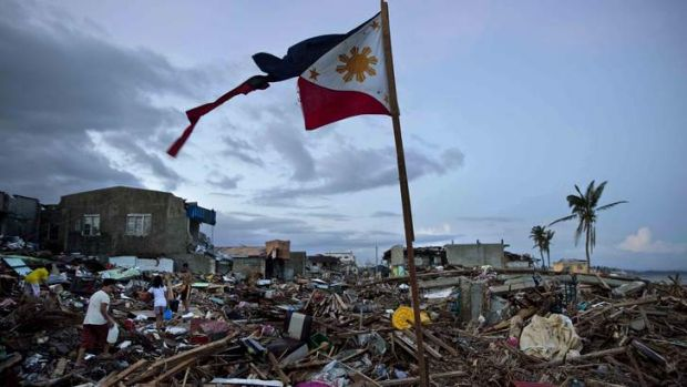 A torn Philippines flag stands in the rubble in the aftermath of Typhoon Haiyan.