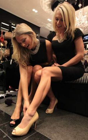 Caroline Pellow, front, and The Bachelor winner Anna Heinrich try on 8cm heels in Sydney.