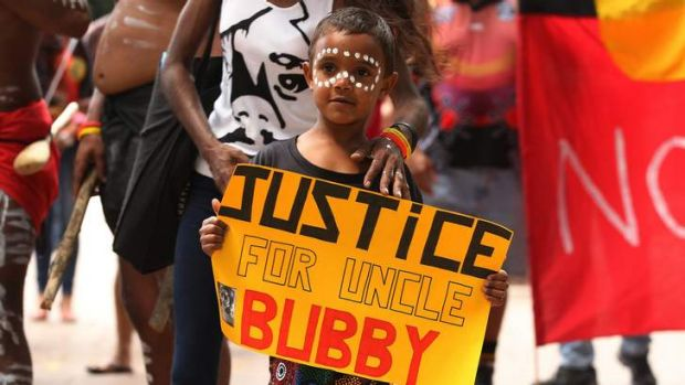 Justice Kirk, five, holds a sign about his uncle Clinton Speedy-Duroux, who was killed aged 16 in 1991.