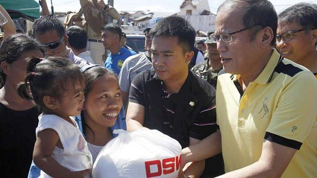 Crisis: Philippine President Benigno Aquino, right, distributes disaster relief items to survivors of Typhoon Haiyan ...