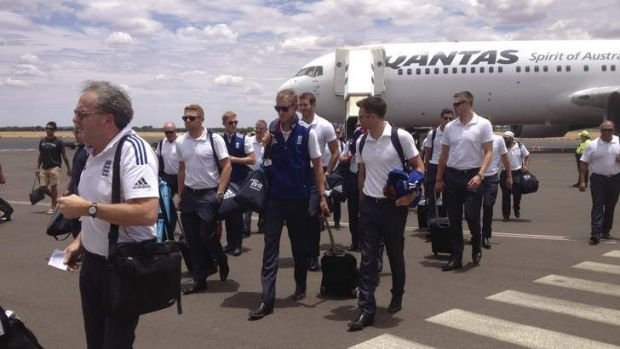 Red centre of attention: Stuart Broad and James Anderson lead the England squad off the tarmac on their arrival in Alice ...