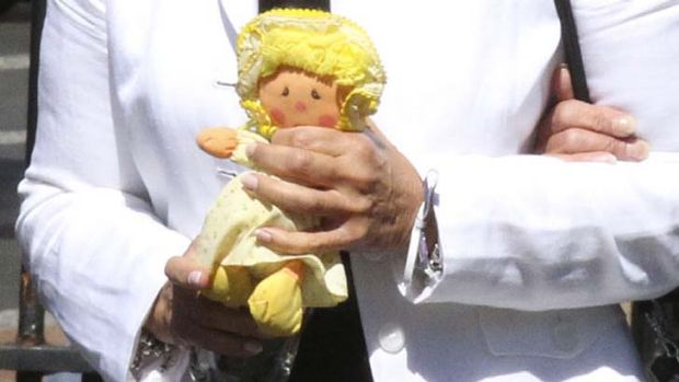 Lisa Harnum's mother, Joan Harnum, carries a doll, believed to have belonged to her daughter, at the NSW Supreme Court ...