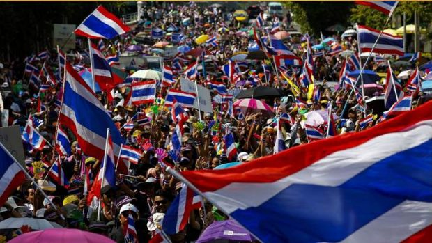 Anti-government protesters wave Thai national flags as they march toward the Labour Ministry in Bangkok.