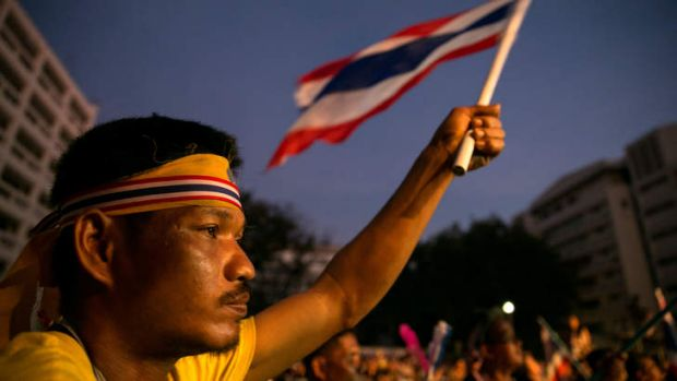 A man holds up a flag and listens to speeches as anti-government protesters occupy the Thai Finance ministry for a third day.