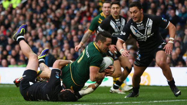 And over: Cooper Cronk of Australia scores after scooping up a kick by Darius Boyd.