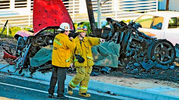First responders gather evidence near the wreckage of a Porsche sports car.