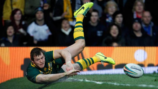 Slip sliding away: Brett Morris eyes an imminent collision with an advertising billboard after scoring a try in ...