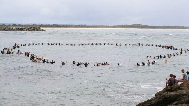 Zac Young's friends form a circle off Port Macquarie's Town Beach to remember him.