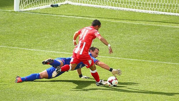 Adelaide United goalkeeper Eugene Galekovic blocks an attempt on goal by Michael Mifsud.