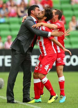 Safe at last: Andrea Migliorini of the Heart celebrates with coach John Aloisi after scoring.