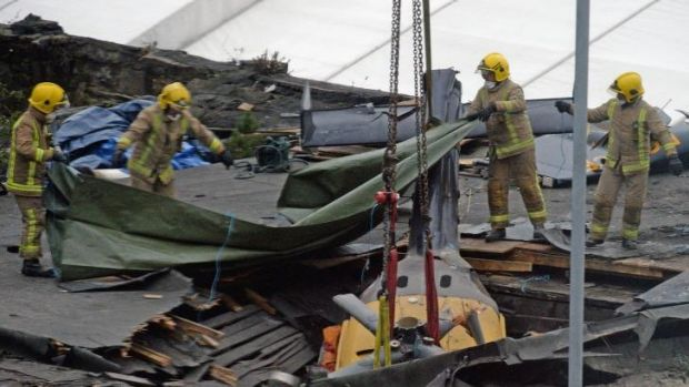 Rescuers lift the police helicopter wreckage from the roof of The Clutha pub in Glasgow.