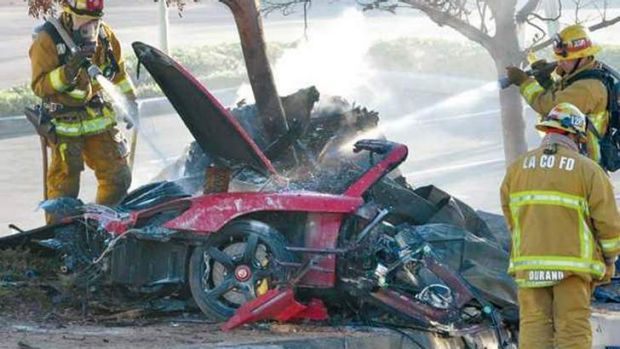 Firefighters extinguish the fire after the crash which killed film star Paul Walker.