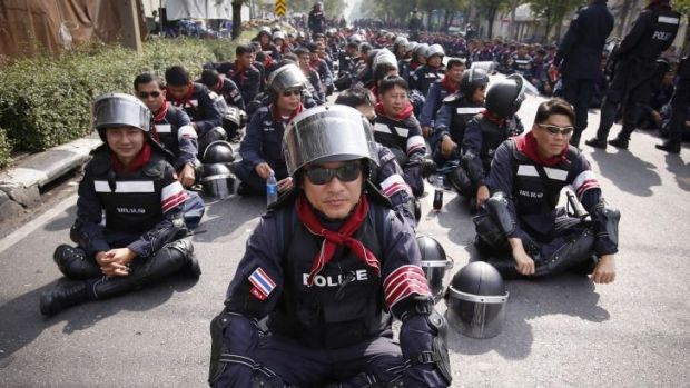 Thai riot police stand down outside the city police headquarters in Bangkok on Tuesday.