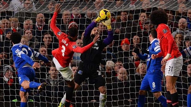 Everton's US goalkeeper Tim Howard (C) saves from Manchester United's French defender Patrice Evra (2L).