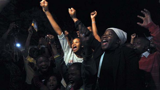 Honouring the legend: Crowds gathered to sing outside Mandela's home in Johannesburg.