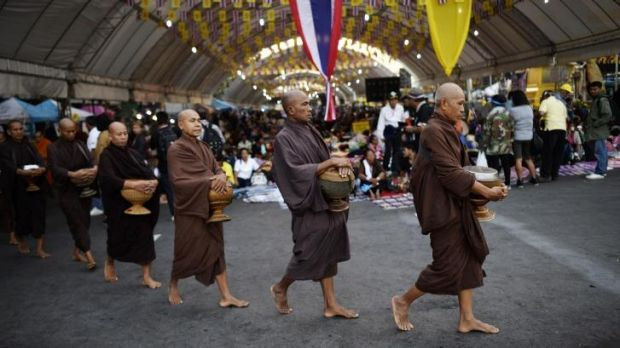 Buddhist monks stroll through an ongoing demonstration by anti-government protesters outside Government House in Bangkok.