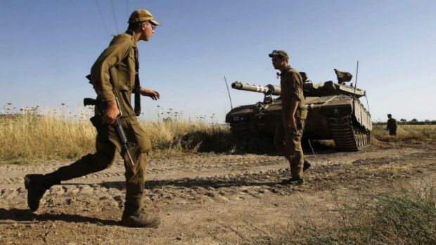 Israeli soldiers walk near a tank in the Israeli occupied Golan Heights near the Quneitra border crossing, close to the ...
